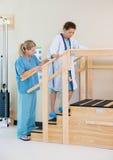 协助移动的治疗师女性患者 免版税库存图片