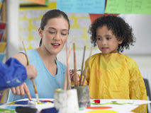 协助绘画的艺术教师逗人喜爱的女孩 免版税库存图片