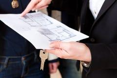 协议夫妇解释租赁资产地产商对年轻人 图库摄影