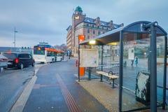 卑尔根,挪威- 2018年4月03日:一个被弄脏的公共汽车站的室外看法与一些公共交通的在街道  免版税库存图片