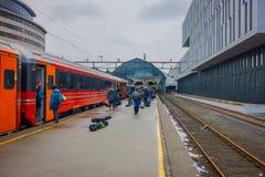 卑尔根,挪威- 2018年4月03日:把火车留在的乘客在平台在卑尔根火车站 库存图片