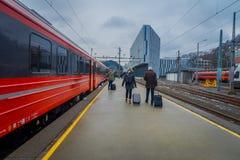 卑尔根,挪威- 2018年4月03日:把火车留在的乘客在平台在卑尔根火车站 库存照片