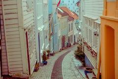 卑尔根,挪威- 2018年4月03日:狭窄的小石中世纪街道在卑尔根市,挪威,有老白色的 库存照片