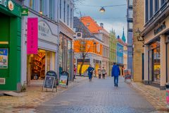 卑尔根,挪威- 2018年4月03日:走在一安静的小巷城市` s保存良好的19世纪的未认出的人民 免版税库存图片
