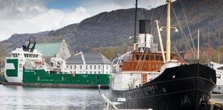 卑尔根,挪威- 2012年5月15日:斯托德岛我减速火箭的船和现代拖轮保守主义者海怪在码头在卑尔根港  免版税库存照片