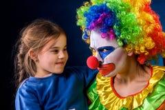单亲家庭 在工作生日小丑以后的妈妈 成人儿童关系 库存图片