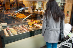 单亲母亲赞赏的法国甜酥皮点心在面包店窗口里 免版税库存照片
