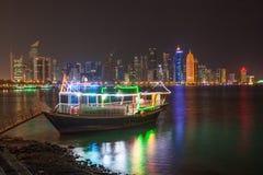 单桅三角帆船和多哈地平线在晚上 库存照片