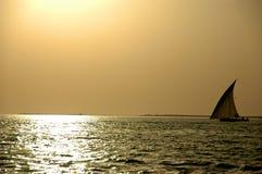 单桅三角帆船日落 免版税图库摄影