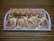单片三明治和点心在盘子,在厨台 库存照片