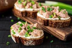 单片三明治用酸奶干酪、罐装金枪鱼和葱在黑木背景 库存图片
