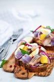 单片三明治smorrebrod用鲱鱼、葱、土豆和鸡蛋 免版税库存图片