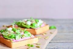 单片三明治用切的鲕梨、新鲜的莴苣、蓬蒿、南瓜籽和奶油在一个木板 与空的地方的背景 免版税库存照片