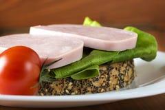 单片三明治用火腿、蔬菜沙拉和一个蕃茄在板材 图库摄影