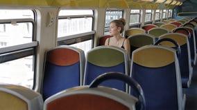 单独一个美丽的白种人女性游人在一列空的客舱地铁乘坐并且看窗口 在她后是 股票视频