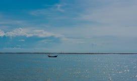 单独一条小的小船在海和蓝天 免版税库存照片