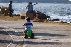 单独乘坐在海边的儿童男孩 图库摄影