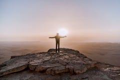 单独人在以色列Neqev沙漠敬佩日出看法  年轻男性收养站立在峭壁边缘 库存照片