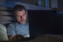 单独人在后显示电子色情的床上使用手提电脑观看的色情性电影在与好色堕落者面孔的晚上 库存照片