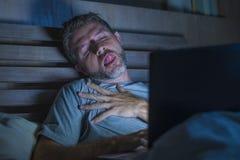 单独人在后显示电子色情的床上使用手提电脑观看的色情性电影在与好色堕落者面孔的晚上 免版税图库摄影