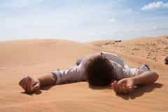 单独人谎言在晴朗的沙漠 他丢失和喘着气 没有水和能量 免版税图库摄影