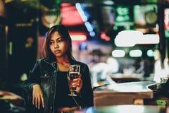 单独俱乐部饮用的啤酒的年轻性感的成人女孩 免版税库存图片