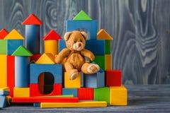 单独减速火箭的熊玩具在与bilding的块的木地板上 库存照片