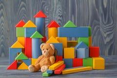 单独减速火箭的熊玩具在与bilding的块的木地板上 免版税库存照片