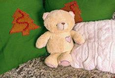 单独减速火箭的熊玩具在用软的枕头装饰的沙发 免版税库存照片