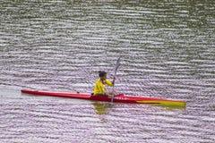 单独划皮船的妇女 皮艇,享用 免版税库存照片