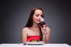 单独吃用酒的美丽的妇女 库存图片