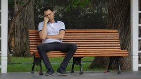 单独哀伤或疲乏的人长凳的 库存图片