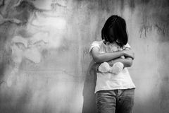 单独哀伤的亚裔女孩有在老墙壁水泥附近的白熊的 免版税库存照片