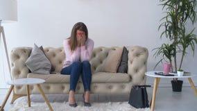 单独哭泣在沙发的沮丧的可爱的妇女 影视素材