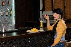 单独喝在酒吧柜台的时髦的妇女 免版税库存照片