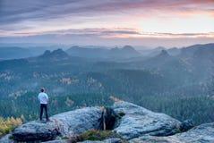 单独图观看从注视着下来狂放的风景的锋利的岩石的日出 库存照片