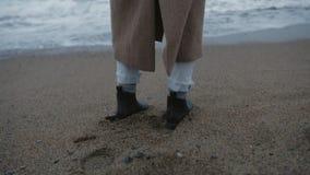 单独在偏僻的海岸的女孩立场与泡沫似的海浪 影视素材