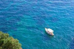 单独在天蓝色的水的白色游艇或小船航行空中顶视图,在蓝色海,阿马飞海岸,意大利 免版税库存图片