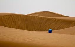 单独坐在一片沙漠的失望的人在迪拜,阿拉伯联合酋长国 免版税库存照片