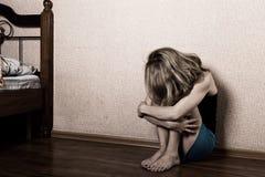 单独坐在一间空的屋子的哀伤的妇女在床旁边 查出的背景国内现有量题头保护自己给新暴力的白人妇女 图库摄影