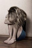 单独坐在一间空的屋子的哀伤的妇女在床旁边 查出的背景国内现有量题头保护自己给新暴力的白人妇女 库存照片