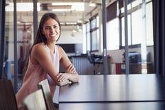 单独坐在会议室里的少妇微笑对照相机 免版税库存照片