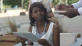 单独坐在咖啡馆桌上的可爱的惊人的年轻美国黑人的夫人,准备做命令 免版税库存照片