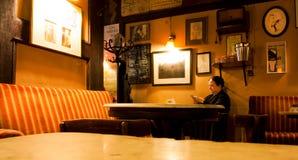 单独坐在咖啡馆的资深妇女 免版税库存图片