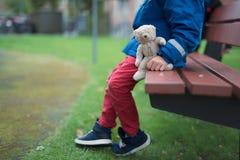 单独坐在有hie玩具熊的一个公园的男孩 免版税库存图片