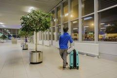 单独坐在机场走廊的年轻男孩在感觉哀伤的心情 库存照片