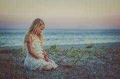 单独坐在海滩的孩子 库存图片