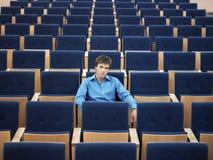 单独坐在观众席的商人 库存图片