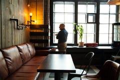 单独坐在顶楼被称呼的咖啡馆的年轻严肃的时兴的人 免版税库存照片