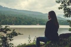 单独坐由河的一名亚裔妇女有天空和山背景 库存照片